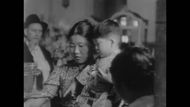 japanese mother holds small male toddler in crowded room in the us during wwii - guerra del pacifico video stock e b–roll