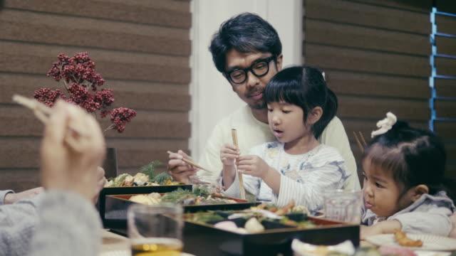 大晦日にオセチリョリを食べる日本の多世代家族 - 飲食点の映像素材/bロール