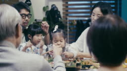 Japanese multi-generation family eating osechi Ryori on New Year's Eve