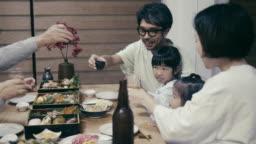 """Japanese multi-generation family saying """"kampai"""" before eating Osechi Ryori on New Year's Eve"""