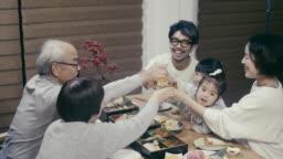 Japanese multig-generation family giving a celebration toast on New Year's Eve