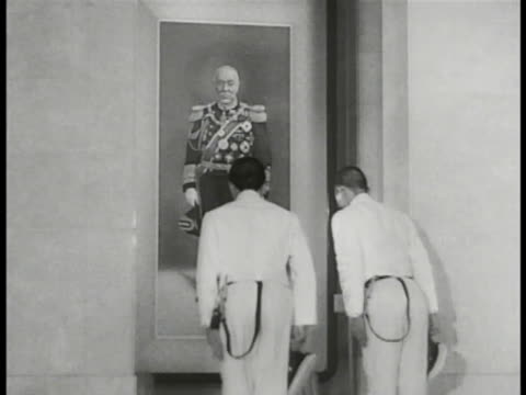 JAPAN Japanese Naval cadet standing in front of painting of Admiral Heihachiro Togo another young soldier joining bowing to painting Both leaving...