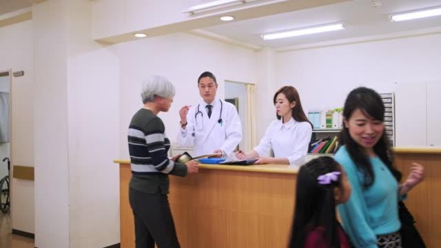 japanska sjuksköterska hjälpa patienten på sjuksköterskor station - sjuksköterskereception bildbanksvideor och videomaterial från bakom kulisserna