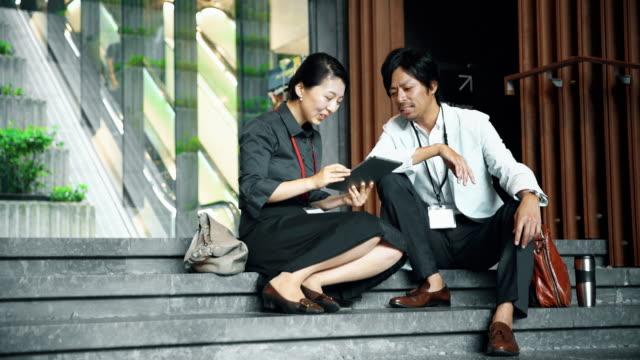 DS japanischen Büroangestellten mit einem Tablet auf der Treppe