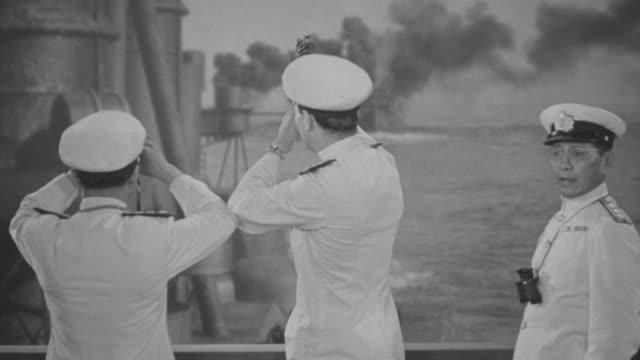 MS Japanese officers and crew on deck of ship as explosions going off