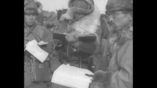 japanese officers, dressed in cold-weather gear, confer / soldiers approach as they depart for chinchow to gain control of the last chinese... - manchuria stock videos & royalty-free footage