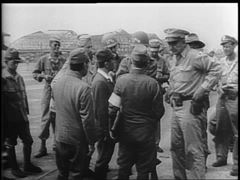 vidéos et rushes de japanese officers walk across atsugi base to meet with general robert eichelberger and other us officers / montage of officers speaking / us troops... - prisonnier de guerre