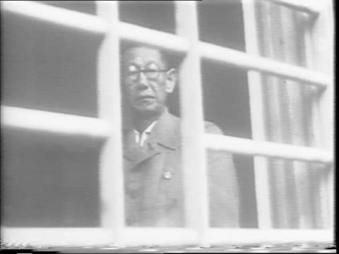 japanese officers walk from a room carrying bags / japanese military officials climb in to the back of a vehicle / the omori prisoner of war camp... - prison camp stock videos & royalty-free footage