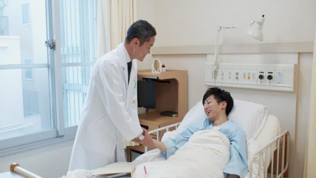 vídeos de stock e filmes b-roll de japanese patient talking to patient in hospital bed and taking pulse - ala hospitalar