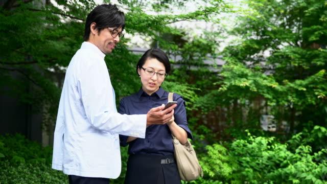 公園でスマート フォンを使用して ds 日本人 - 土曜日点の映像素材/bロール