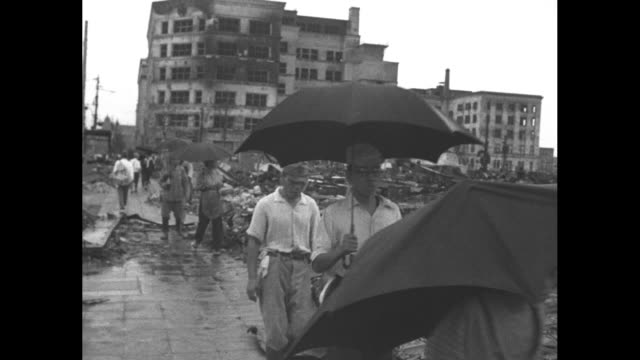 japanese people walking through building debris, then pan through wreckage / japanese with umbrellas walk through wreckage / soldiers and civilians... - guerra del pacifico video stock e b–roll