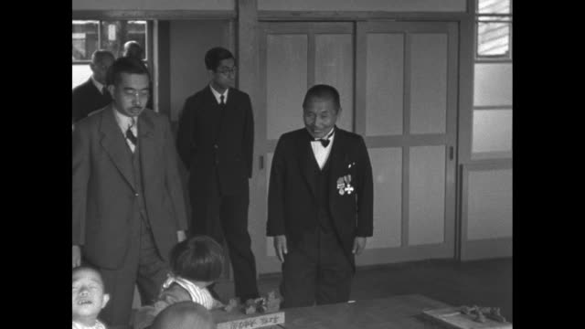 japanese police locked arminarm hold back crowd / carvings of animals /emperor hirohito wife princess nagako and entourage enter room with small... - japanese royalty stock videos and b-roll footage