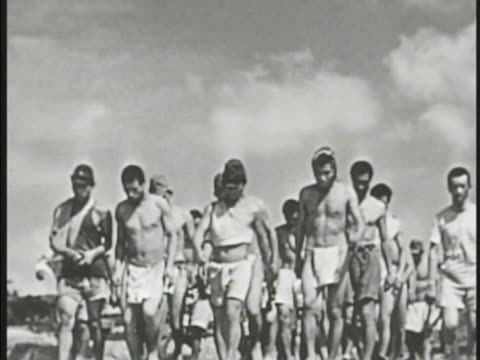 Japanese POW soldiers in little clothing walking in groupMS American flag lowering to half mast on pole Pacific Theater WWII World War II