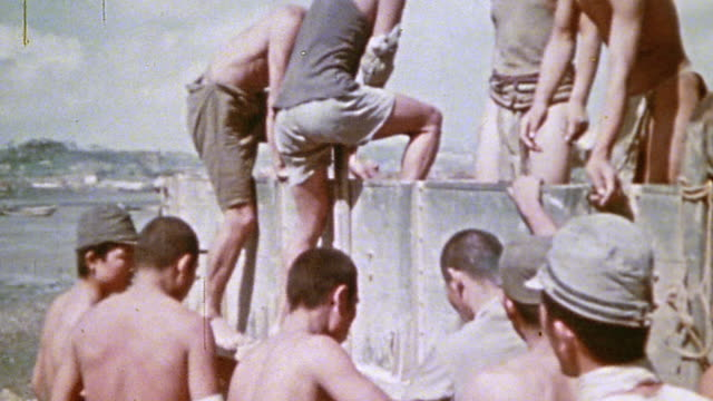 japanese prisoners and civilians climbing into a military truck and standing in formation while 6th division marines keep watch / okinawa japan - prisoner of war stock videos & royalty-free footage