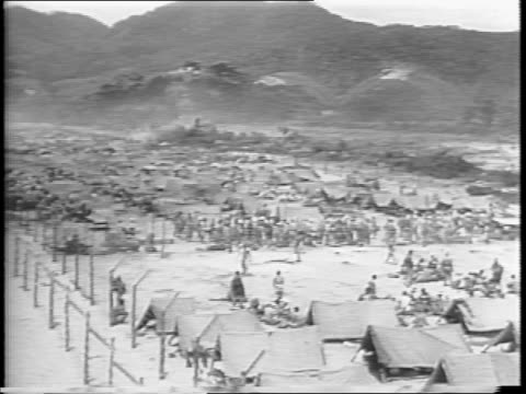 japanese prisoners walk among tents in an american prison camp in japan / mass crowd of prisoners in camp seated / prisoner smiles and one smokes - 1945 stock videos & royalty-free footage