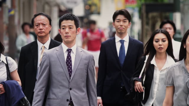 vidéos et rushes de japanese professionals walk past the camera - homme d'affaires