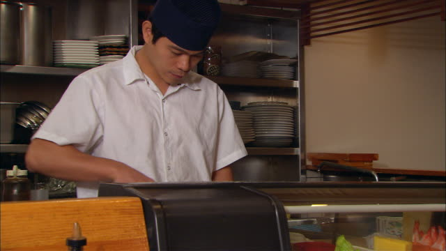 cu, japanese restaurant chef preparing food behind display cabinet - display cabinet stock videos & royalty-free footage