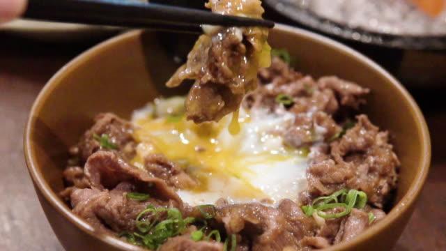 japanese rice bowl with egg yolk and gyudon wagyu beef. - egg yolk stock videos & royalty-free footage