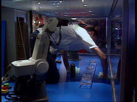 japanese robot exhibition; 13.00 england: london: science museum men at work sawing man polishing display cabinet cms four legged experimental... - display cabinet stock videos & royalty-free footage