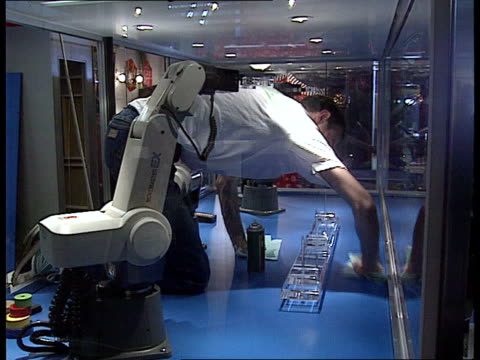 London Science Museum MS Men at work sawing MS Man polishing display cabinet CMS Four legged experimental walking robot PULL OUT Ditto