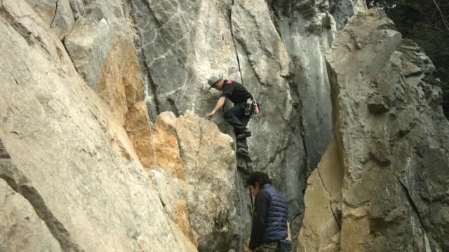 vídeos y material grabado en eventos de stock de a japanese rock climber and belayer work together - artículo de montañismo