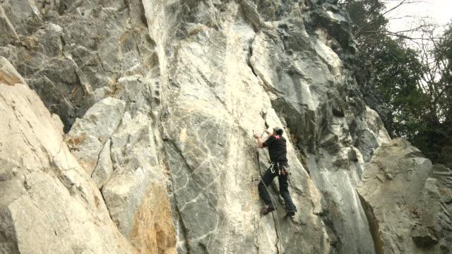 vídeos de stock, filmes e b-roll de a japanese rock climber climbs up a large crack in the rock face - gancho de alpinismo