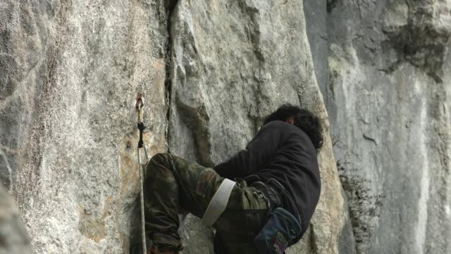 a japanese rock climber climbs up a limestone rock face - 挑戦点の映像素材/bロール