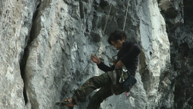 a japanese rock climber descending and removing climbing gear - climbing equipment stock videos and b-roll footage