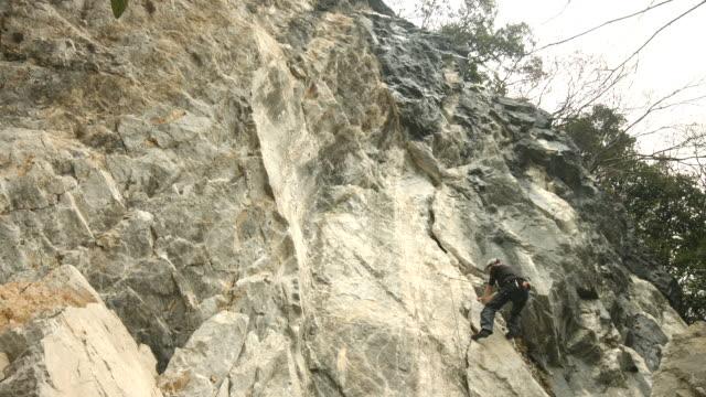 vídeos de stock, filmes e b-roll de a japanese rock climber scales a limestone rock face - gancho de alpinismo
