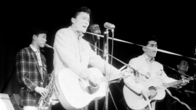 japanese rockabilly band performing for teenage audience / streamers cover lead singer / lead singer falls on ground while playing guitar / female... - 1958 stock videos & royalty-free footage