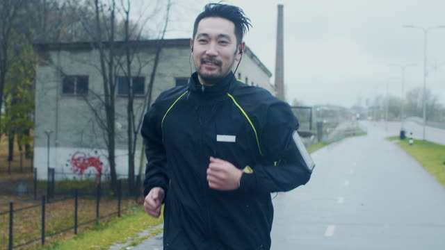 stockvideo's en b-roll-footage met japanse runner in de regen (slow motion) - hoofdtelefoon