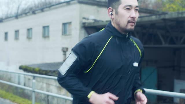 雨の中 (スローモーション) で日本のランナー - jogging点の映像素材/bロール