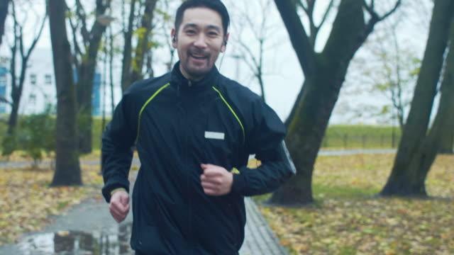 vídeos de stock e filmes b-roll de japanese runner in the rain (slow motion) - praticar