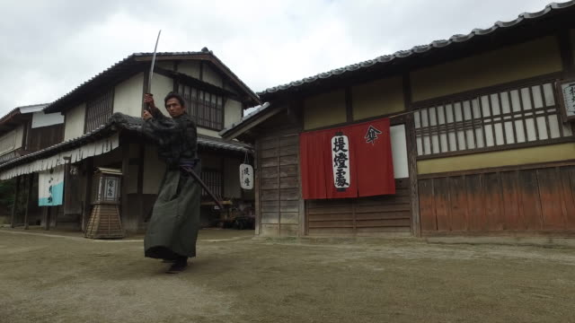 vídeos de stock e filmes b-roll de japanese samurai with his sword in the village streets - samurai