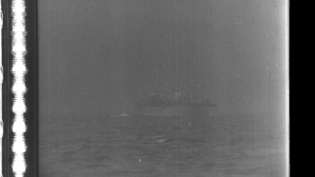 japanese shells hit a british cargo ship which sinks while its merchant seamen crew abandon ship and take to lifeboats - sink stock videos and b-roll footage