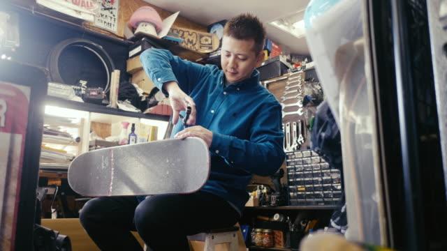 japanischer skateboard-shop-besitzer, der ein skateboard repariert - anpassen stock-videos und b-roll-filmmaterial