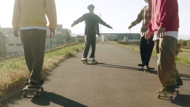 japanese skateboarders skating in the sunset (slow motion) - teenage boys stock videos & royalty-free footage