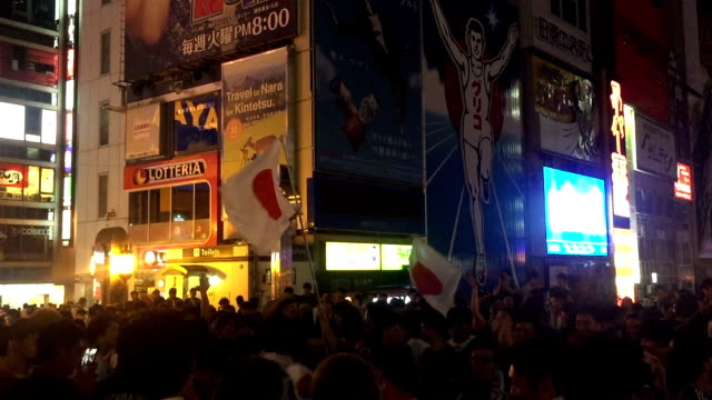 japanese soccer fans celebrating at dotonburi bridge in osaka , japan . - fifa world cup stock videos & royalty-free footage