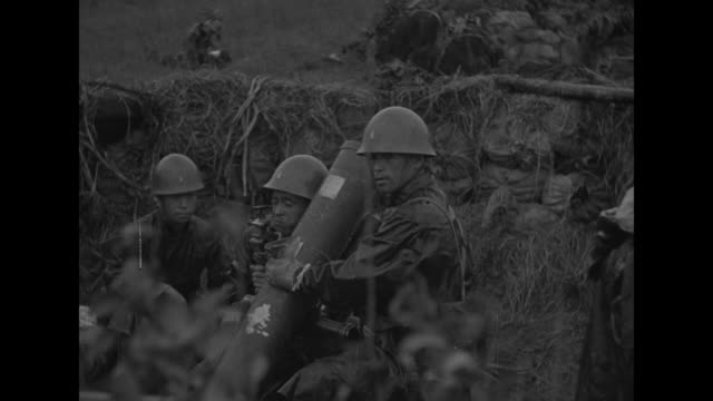 japanese soldier looks through field glasses as another stands by / soldiers sit with large weapon / rear shot soldiers look out from sandbag bunker... - bomb shelter stock videos & royalty-free footage