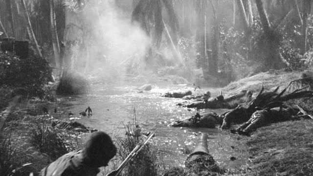 MS PAN POV Japanese soldiers at war in jungle and they crossing stream