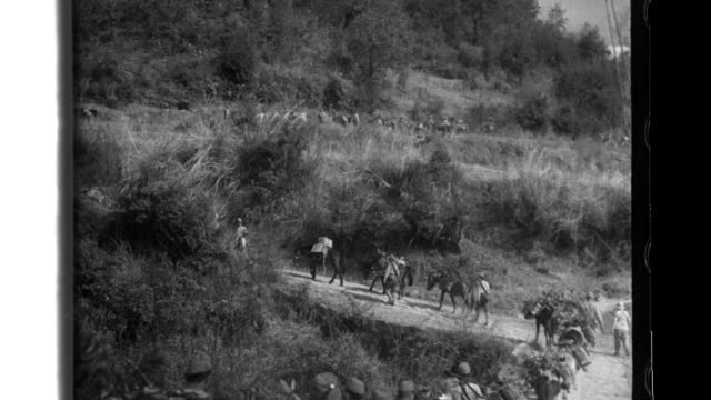 Japanese soldiers climb steep mountain terrain on the BurmaChina border infantrymen attack with machine guns and grenade dischargers they struggle...