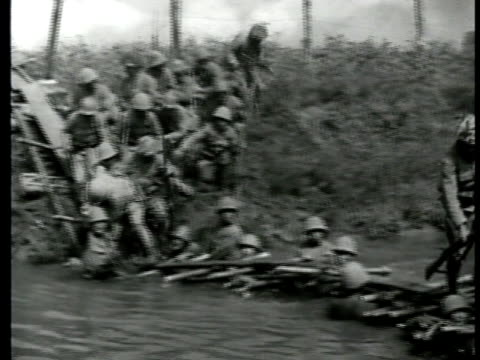 stockvideo's en b-roll-footage met japanese soldiers crossing plank bamboo bridge soldiers in water holding bamboo crosssupports on shoulders cu soldiers w/ bamboo on shoulders w/... - 1943