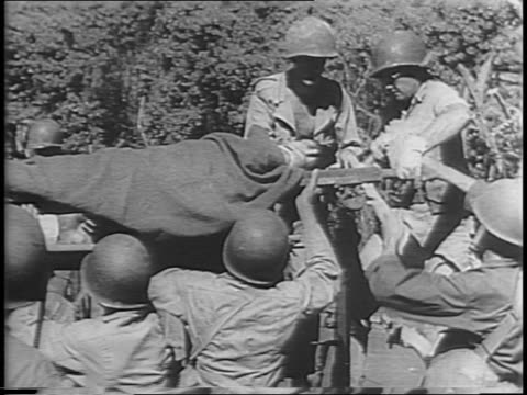 japanese soldiers lie dead in sand / american wounded are carried on stretchers / dead us soldier lies face down on stretcher / soldier squats and... - stretcher stock videos and b-roll footage
