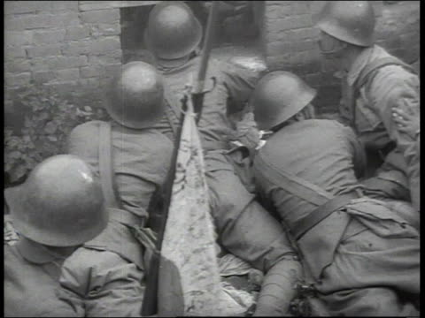 japanese soldiers lying on bellies peering through opening in what remains of the wall of a building that has been reduced to rubble / china - rubble stock-videos und b-roll-filmmaterial