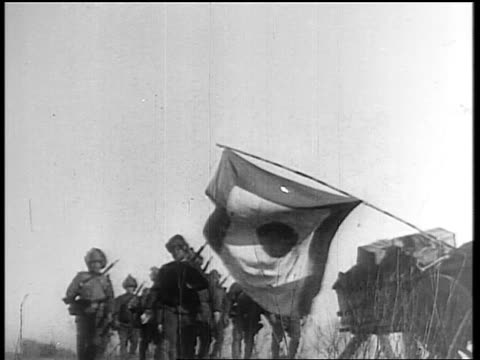 Japanese soldiers marching behind cart with Japanese flag / Japan invading Manchuria