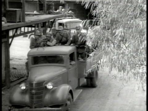 Japanese soldiers on back of trucks driving through town Beijing Second SinoJapanese War World War II