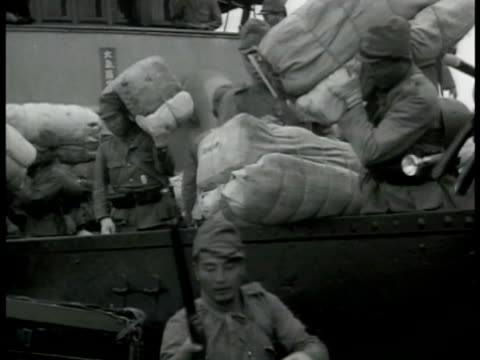 japanese soldiers on transport ship coming into dock. soldiers unloading cargo weapons. two small transport ships in dock. large transport ships in... - 1942年点の映像素材/bロール