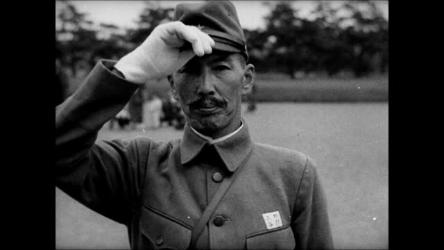 japanese soldiers walking by army post. officer taking off hat bowing. emperor of japan hirohito on horseback w/ aides. japanese soldiers bowing.... - 昭和天皇点の映像素材/bロール