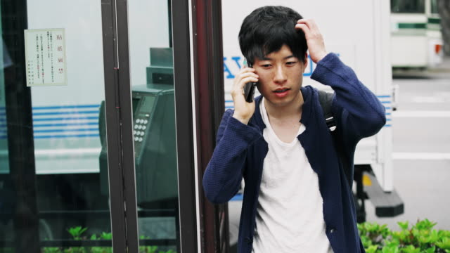 De Japanse student MS op de mobiele telefoon naast de telefooncel