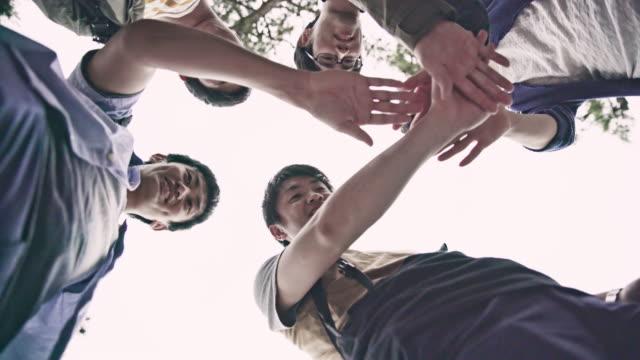 ms ラの日本人学生が一緒に彼らの手を置く - istockalypse点の映像素材/bロール